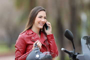 Happy motorbiker calling on phone on a motorbike