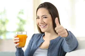 Satisfied consumer holding an orange juice glass