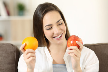 Woman deciding between orange and apple at home