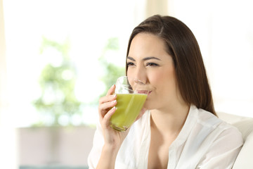 Woman drinking a green vegetable juice at home