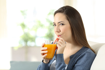 Woman drinking orange juice with a straw