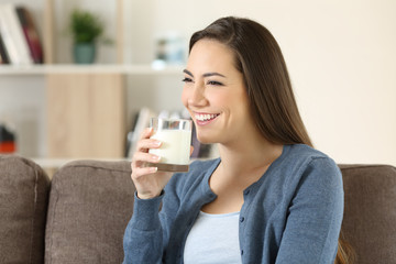 Woman holding a glass of milk on a couch