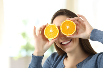 Woman joking with two half orange slices