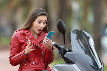 Amazed motorbiker reading exciting news on line