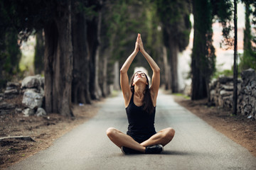 Carefree calm woman meditating in nature.Finding inner peace.Yoga practice.Spiritual healing lifestyle.Enjoying peace,anti-stress therapy,mindfulness meditation.Positive energy.Controling mind