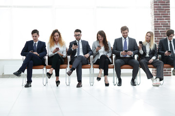 employees with smartphones sitting in the lobby