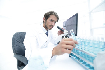 Chemist looking at test-tubes with blue liquids