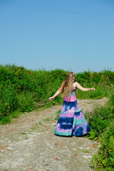 white caucasian blonde girl with colorful long dress dances on a dirt road in field