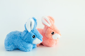 pink and blue toy Easter bunnies facing right isolated on a solid background