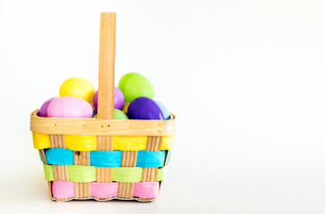 wicker Easter basket with colorful weaved ribbons filled with plastic Easter eggs isolated on white
