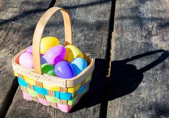 wicker Easter basket filled with colorful plastic Easter eggs on a rustic wooden table in morning sunlight