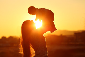 Mother raising her kid son at sunset with the sun in the middle