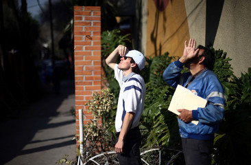 Men look up at a building being demolished five months after the September 19 earthquake, in the Colonia Doctores neighborhood in Mexico City