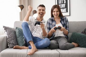 Young couple playing video games at home Wall mural