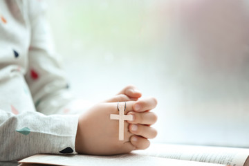 Religious Christian girl praying over Bible indoors, closeup