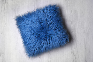 Fluffy pillow on wooden floor