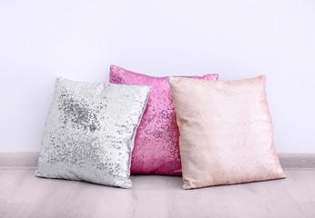 Shiny decorative pillows on wooden floor near wall