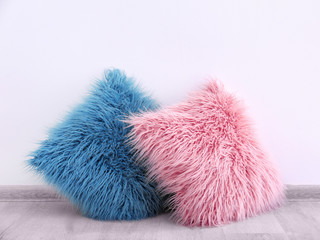 Two fluffy pillows on wooden floor near wall