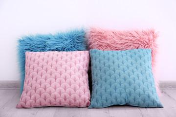 Stylish pillows on wooden floor near wall