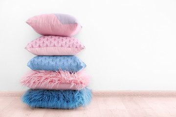 Stack of stylish pillows on wooden floor near wall