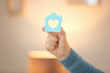 Senior woman holding house figure on blurred background. Home care concept