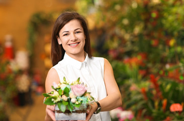 Portrait of young woman with flowers in greenhouse. Small business owner