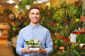Portrait of young man with flowers in greenhouse. Small business owner