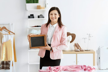 Portrait of young woman with mini chalkboard in atelier. Small business owner