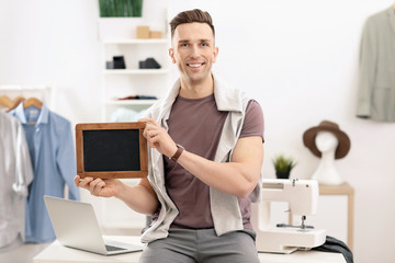 Portrait of young man with mini chalkboard in atelier. Small business owner