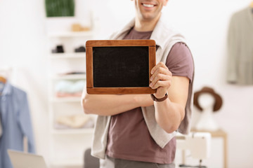 Man holding mini chalkboard in atelier. Small business owner