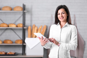 Portrait of young woman in bakery. Small business owner