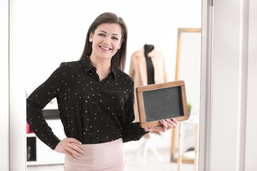 Portrait of young woman with mini chalkboard in boutique. Small business owner