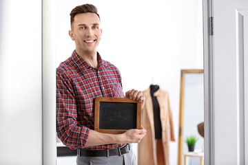 Portrait of young man with mini chalkboard in boutique. Small business owner