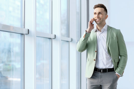 Young man talking on phone in office. Small business owner