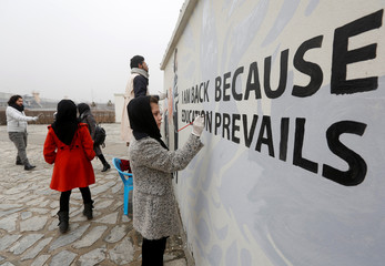 Afghan Artlords paint a message on a wall at the American University of Afghanistan in Kabul