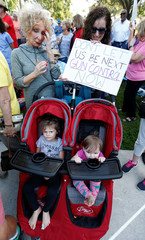 Protester Abigail Langweiler holds a sign as her children sit in a stroller during a Call To Action Against Gun Violence rally by the Interfaith Justice League and others in Delray Beach