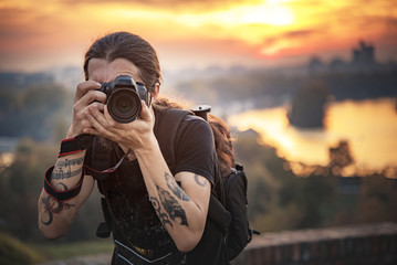 Young photographer with long hair and alternative style taking photographs with his dslr camera, capturing landscape and sunset in a park