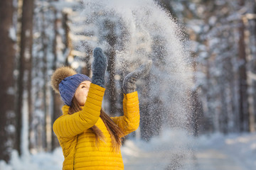 Portrait of young smiling woman throws up a snow in a winter forest