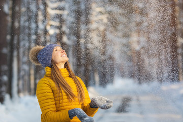 Portrait of young smiling woman looking to falling snow in a winter forest