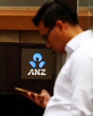A man uses his mobile phone in front of an ANZ bank branch in central Sydney