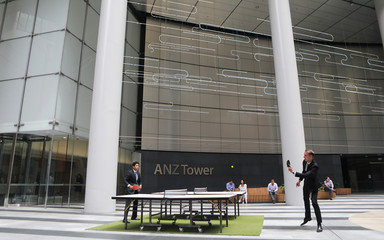 Office workers play table tennis in front of an ANZ Banking corporation tower in central Sydney
