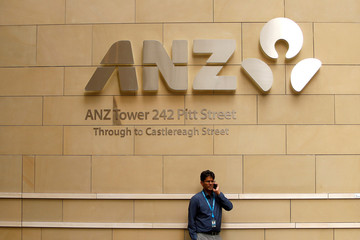 A man talks on his phone in front of an ANZ Banking corporation tower in central Sydney