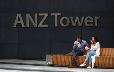Office workers eat lunch in front of an ANZ Banking corporation tower in central Sydney