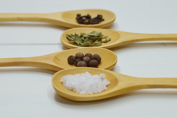 four wooden spoons with spices side view