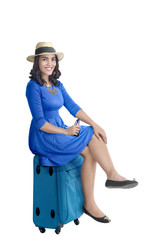 Portrait of asian woman with hat sitting on suitcase