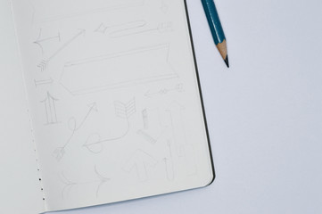 notebook with pencil sketches of arrows on white background