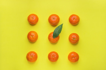 Bright Ripe Tangerines Arranged in Rows in Square One with Green Leaf in Middle. Yellow Background. Food Knolling. Styled Creative Image. Tropical Fruit Vacation Summer Vegan Concept