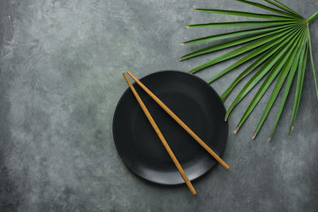 Black Empty Plate with Brown Bamboo Chopsticks Pal Tree Leaf on Dark Grey Stone Background. Asian Thai Chinese Cuisine Concept. Menu Poster Recipe Template. Copy Space