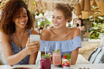 Photo of pleasant looking African American female blogger shows her own web site on cell phone to friend, shares great success and many followers. Happy women watch funny pictures on mobile phone