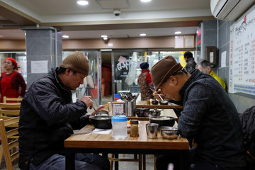 Men eat traditional oxtail soup at the Jungang Market in Gangneung